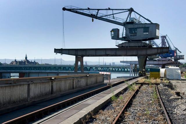 Ein Hafenkran wird vom Hafen St. Johann in den Klybeckquai versetzt. Bild: Keystone